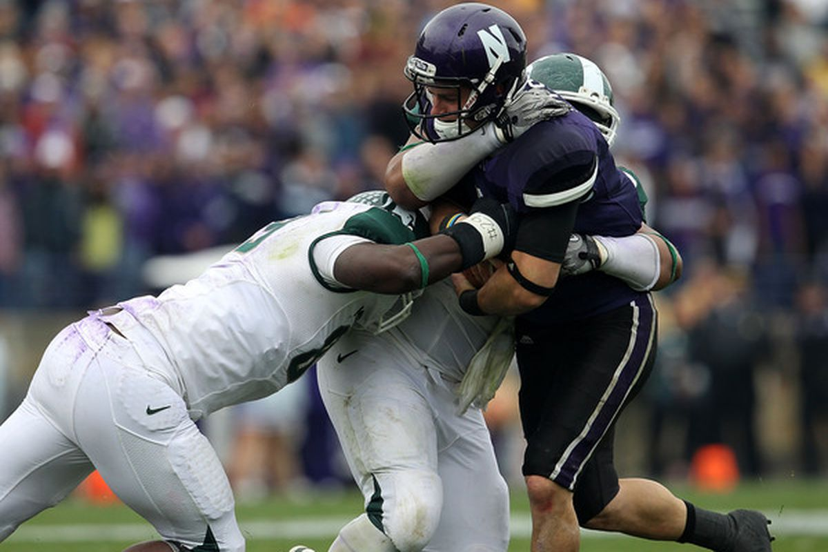 Dan Persa of the Northwestern Wildcats is stopped by Colin Neely and Jerel Worthy of the Michigan State Spartans at Ryan Field on October 23 2010 in Evanston Illinois. (Photo by Jonathan Daniel/Getty Images)