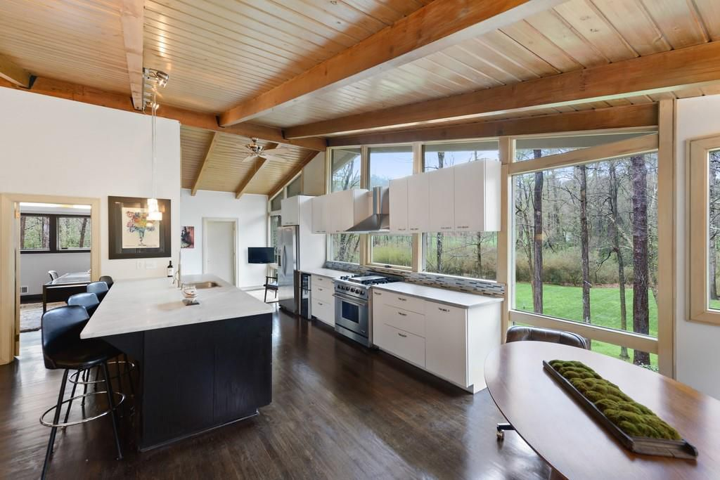 A large white kitchen with many windows.