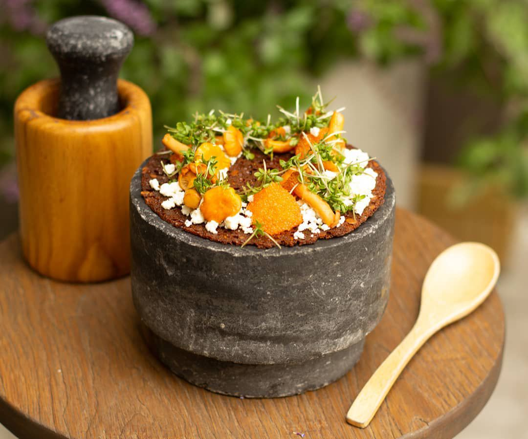 A rye pancake sits on a large stone platform topped with mushrooms, sour cream, shallots, and dill, beside a mortar and pestle and wooden spoon