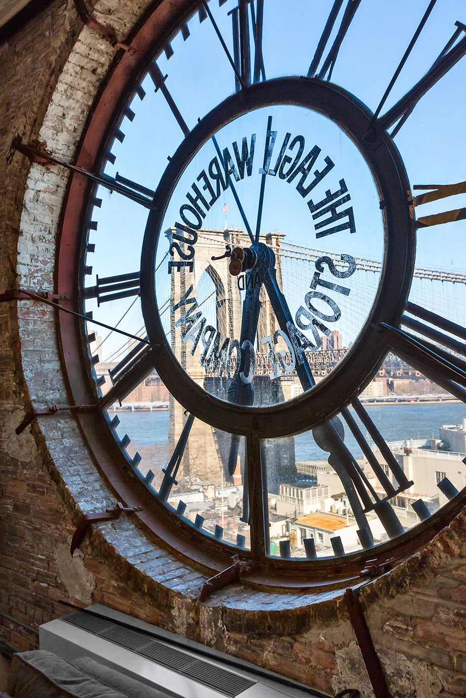 A transparent clock surrounded by exposed brick, with views of the Brooklyn Bridge.