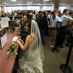 Heather Collins, front, and Jax Collins apply for a marriage license at the Salt Lake County clerk's office, Monday, Dec. 23, 2013. U.S. District Judge Robert Shelby denied a motion by the state of Utah to halt same-sex marriages pending an appeal.