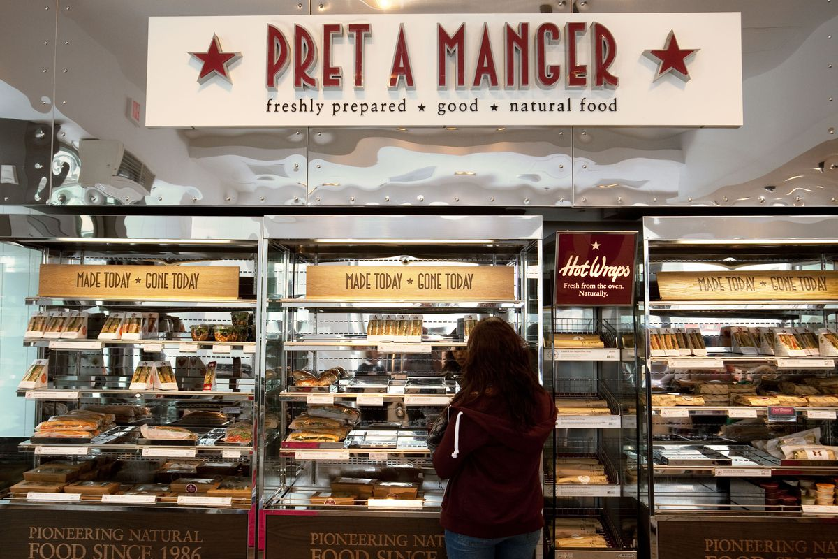 """A view of Pret a Manger's sandwich and """"hot wrap"""" shelves, with the brand's maroon logo in large capital letter above the food"""