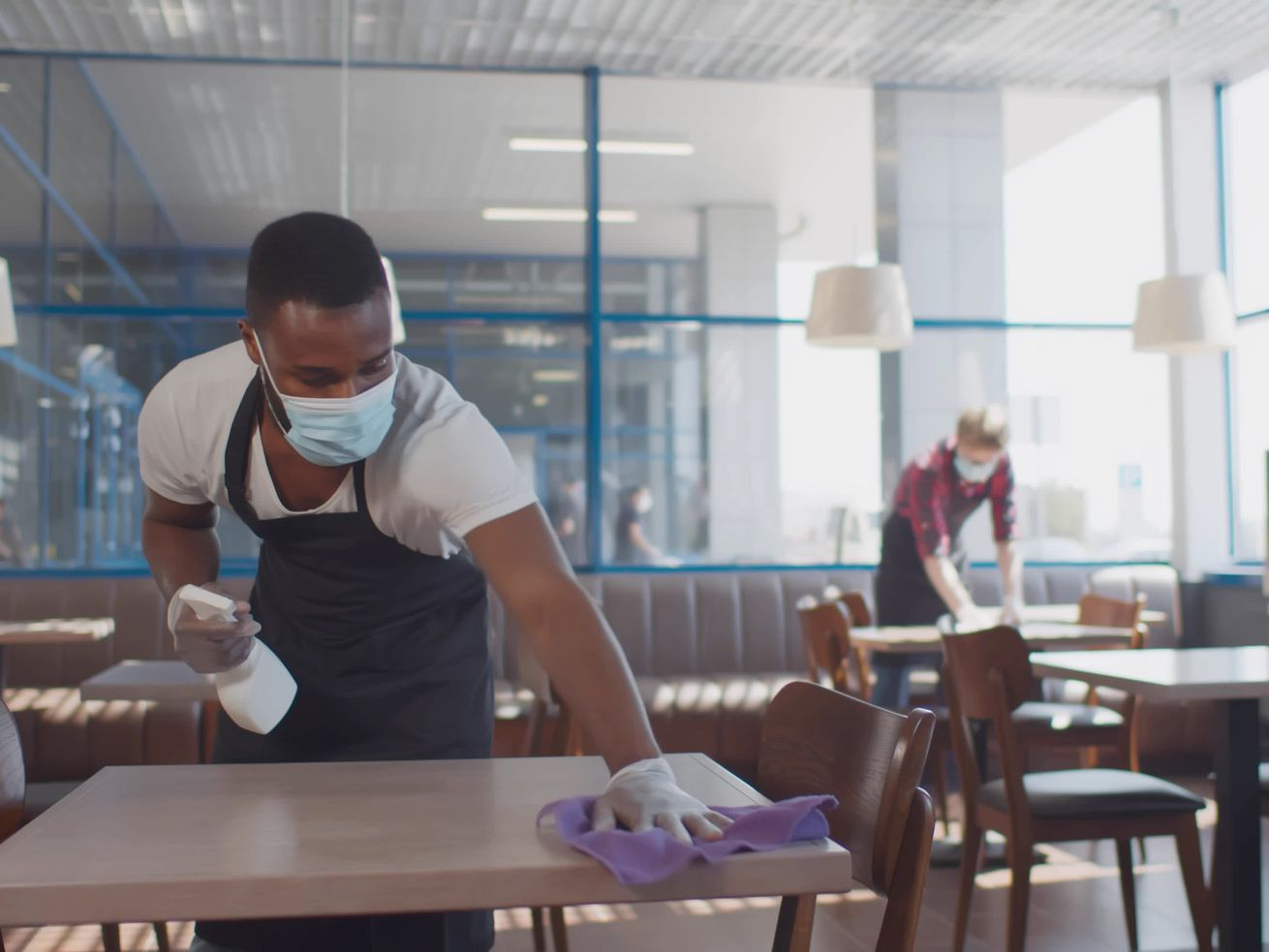 Two masked, gloved restaurant workers clean tables inside an empty restaurant dining room.