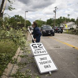 A resident carries a speed limit sign on Janes Avenue near Evergreen Lane in Woodridge after a tornado ripped through the western suburbs overnight, Monday morning, June 21, 2021.