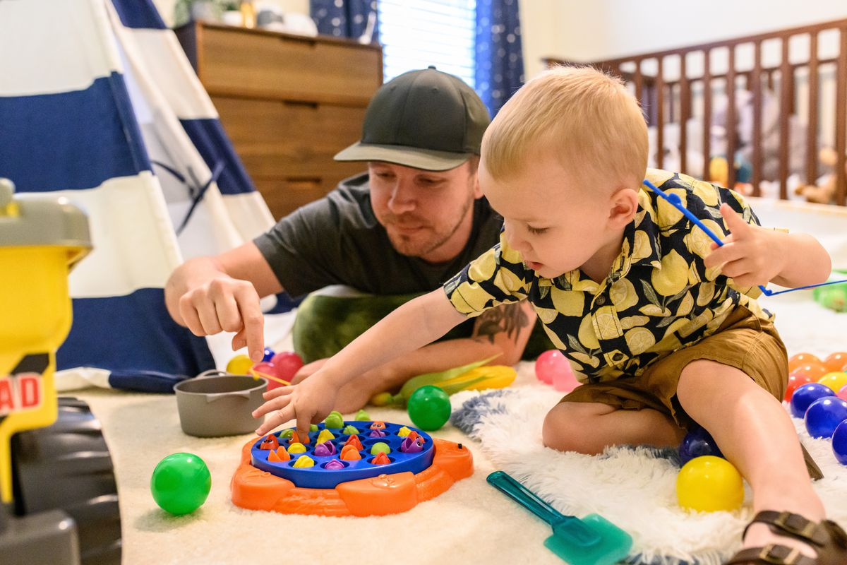 Toddler on the floor playing with a game; man wearing baseball hat sits next to him and plays along.