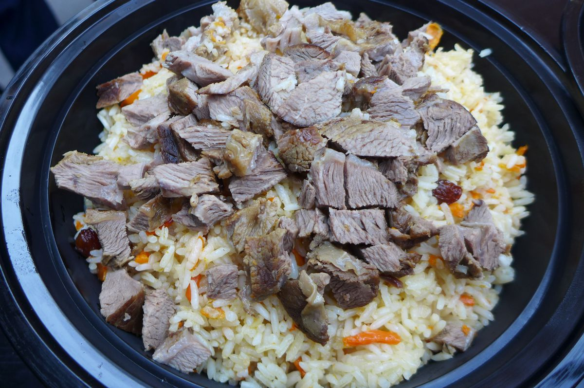 Rice and carrots with small chunks of lamb on top.