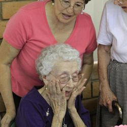 In this March 30, 2012, photo, Verla Morris, who will turn 100 later this year, is surprised with an early 100th birthday cake, presented to her by Maria Anaya, the resident manager, at Morris's local residential senior center, in Chandler, Ariz. When the 1940 census records are released Monday, April 2, Morris will see her own name and details about her life in the records being released after 72 years of confidentiality expires, allowing her to find out more about her family tree.