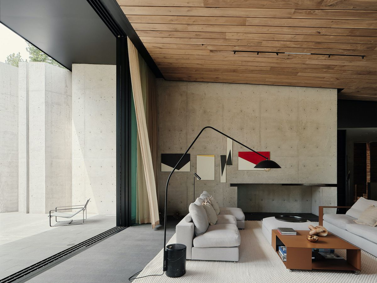 Living room featuring concrete walls and timber paneled ceiling.
