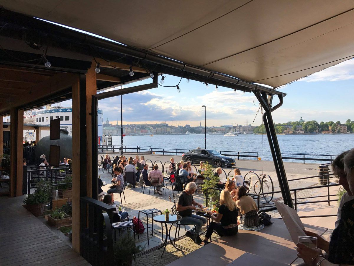 A crowded restaurant patio extending out from covered awnings toward a boardwalk and water beyond