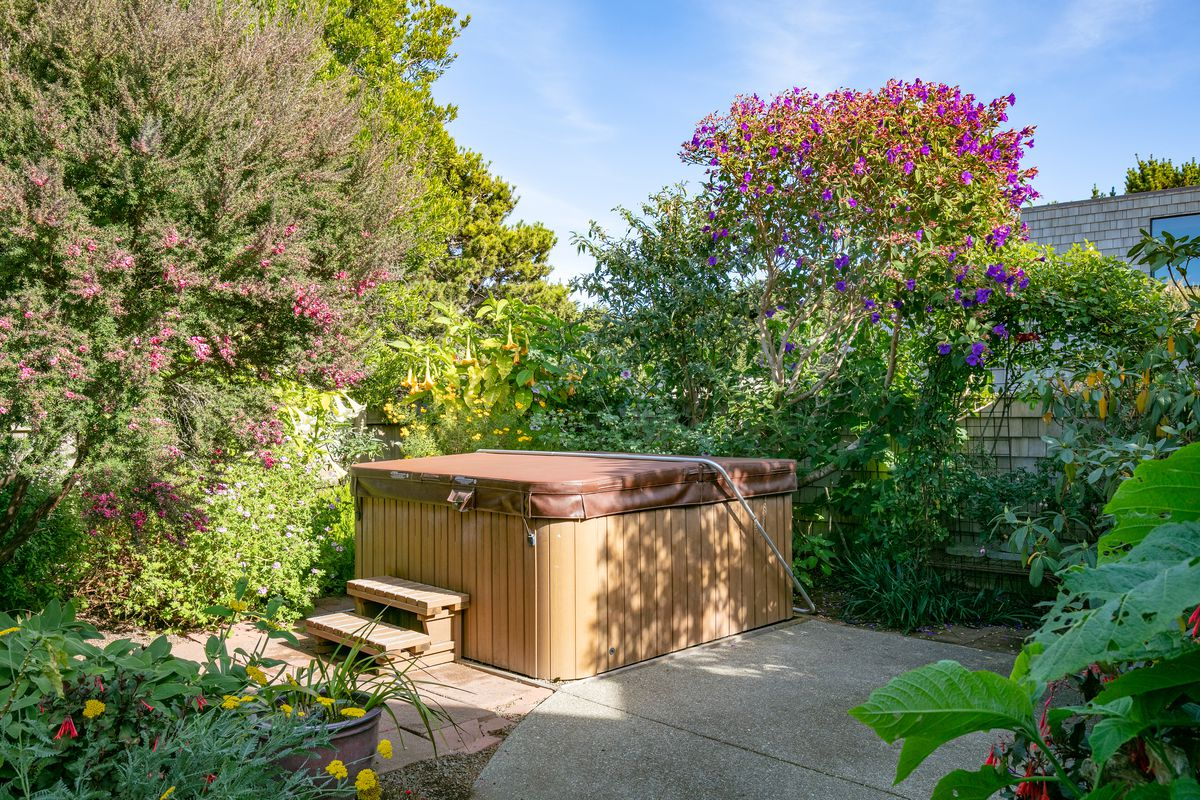 A backyard hot tub surrounded by blooming trees and plants to give privacy from the house behind it.