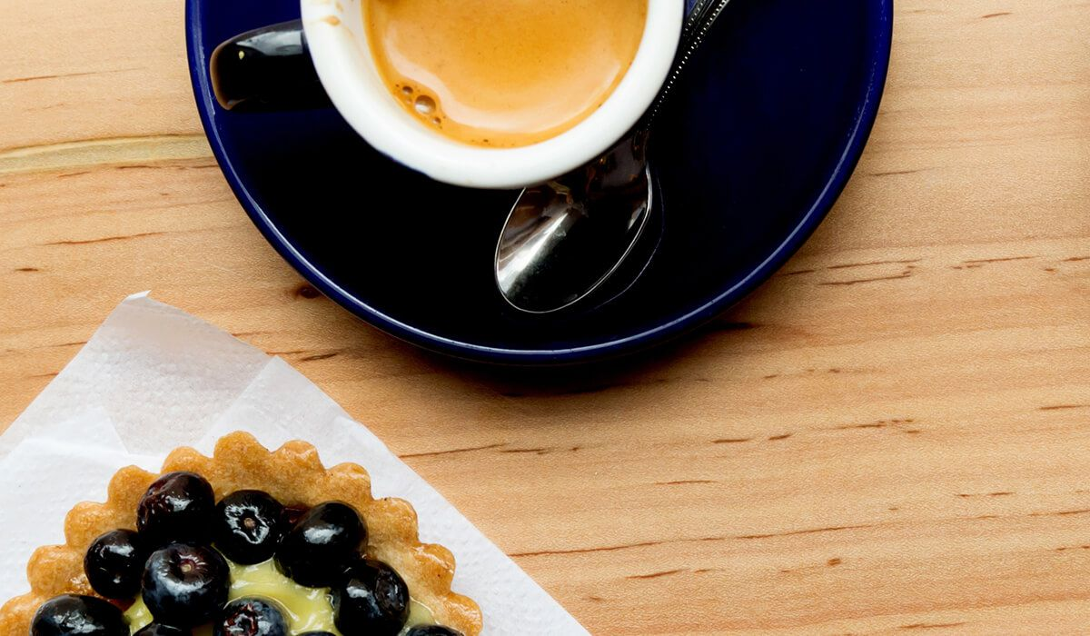 The edge of a blueberry-covered pastry is visible on one edge of the photo, and a small cup of a coffee beverage is visible on another edge