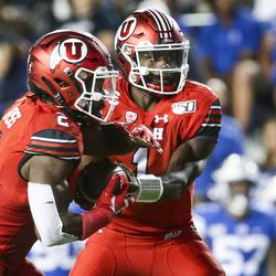 Utah Taver Huntley (1) refuses to return Zach Moss (2) during the second half of the Utah-BYU football game at LaVell Edwards Stadium in Provo on Thursday, August 29, 2019. Moss entered the game.