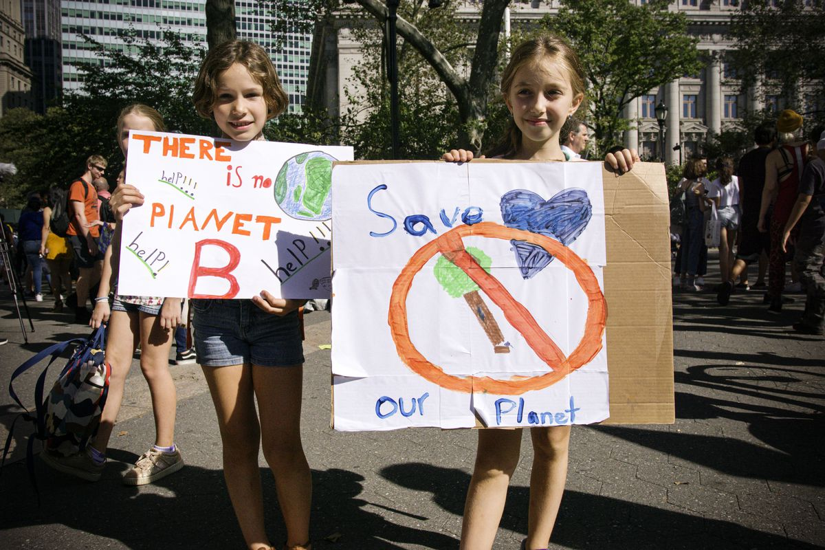 """Two girls hold protest signs at the Global Climate Strike in New York City. The signs read, """"There is no planet B, help! help!"""" and, """"Save our planet"""" with a drawing of a tree being cut down under a circle with a line through it."""