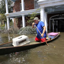 Don Duplantier paddles a pirogue from his flooded home as floodwaters from Hurricane Isaac recede in Braithwaite, La., Sunday, Sept. 2, 2012. Duplantier had retrieved his cat and had collected his daughter's bridesmaid dress for the upcoming wedding of his son.