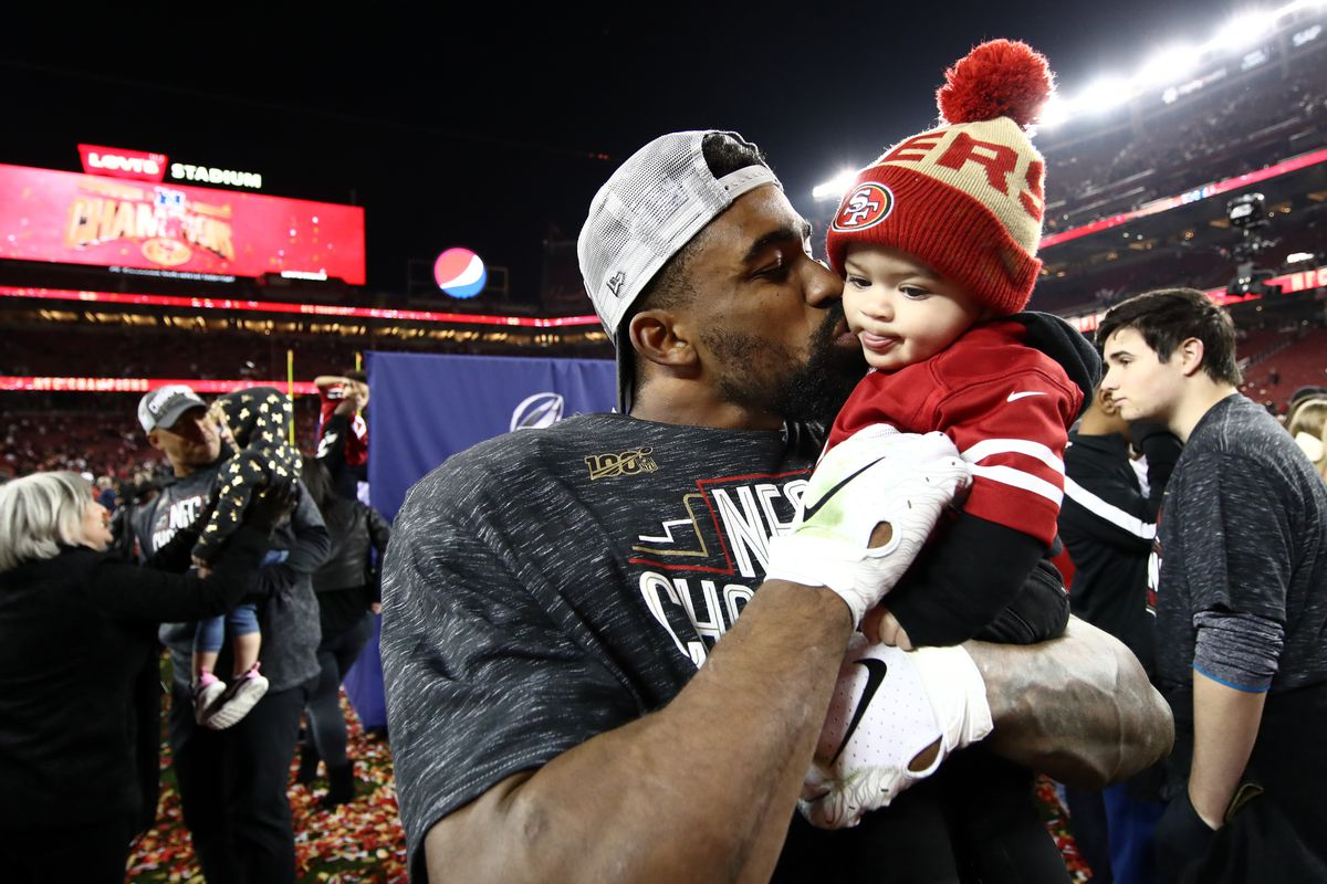 Raheem Mostert #31 of the San Francisco 49ers celebrates with his son, Gunnar, after winning the NFC Championship game against the Green Bay Packers at Levi's Stadium on January 19, 2020 in Santa Clara, California. The 49ers beat the Packers 37-20.