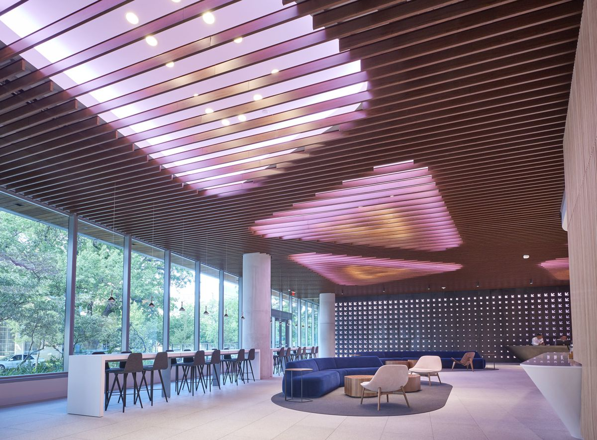 Contemporary open lobby with streetfacing windows, triangle-shaped pinkish overhead lights breeze block wall long high table with high chairs modern furniture