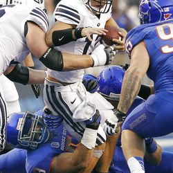 Riley Nelson (13) of the Brigham Young Cougars is tackled by Beau Martin (53) of the Boise State Broncos during NCAA football in Boise, Thursday, Sept. 20, 2012.
