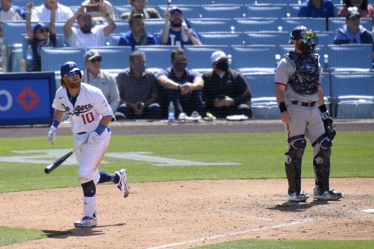 Justin Turner #10 of the Los Angeles Dodgers watches his solo homerun with Jonathan Lucroy #28 of the Washington Nationals, for a 1-0 lead in the sixth inning, during the 2021 MLB season home opening game at Dodger Stadium on April 09, 2021 in Los Angeles, California.