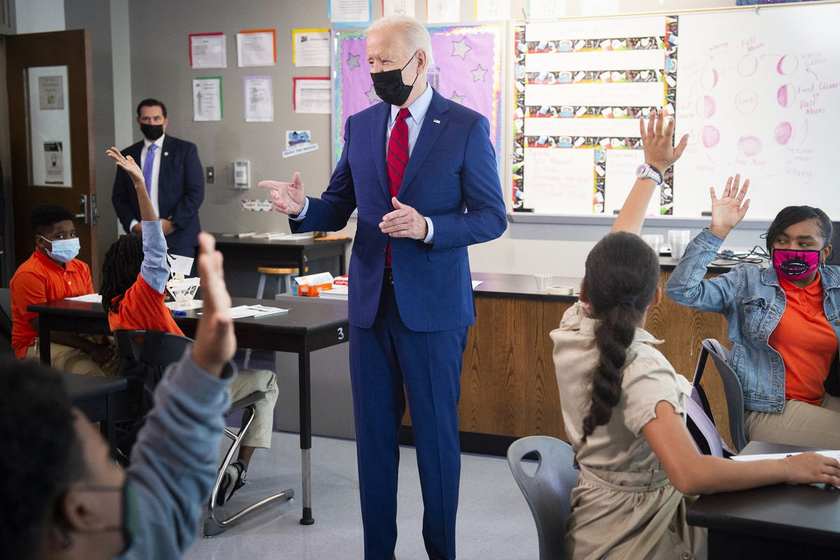 President Biden stands in a middle school classroom where several students are seated and raising their hands.