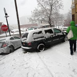 Pedestrians walk around an accident on South Temple in Salt Lake City on Thursday, Dec. 19, 2013.