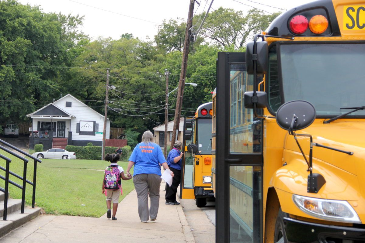 Riverside teachers and staff help students find the right buses at the start of the school year.