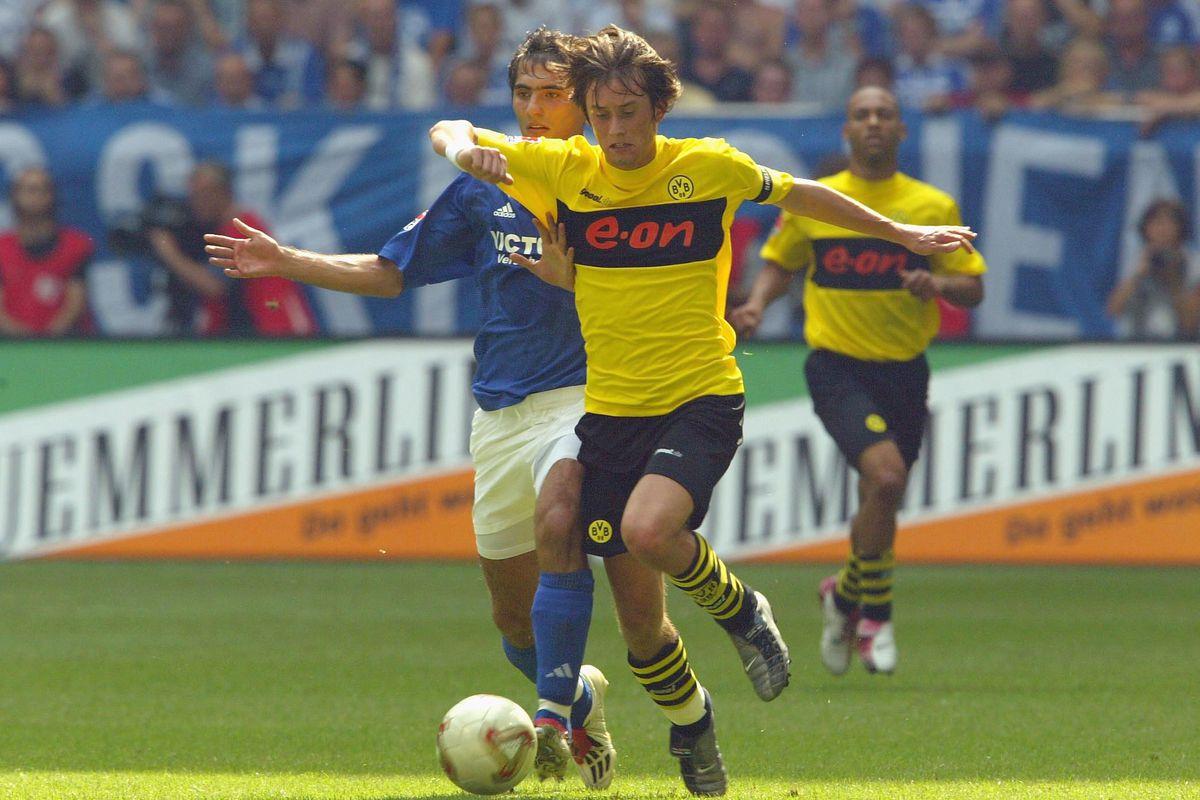 Hamit Altintop of Schalke tussles with Thomas Rosicky of Dortmund