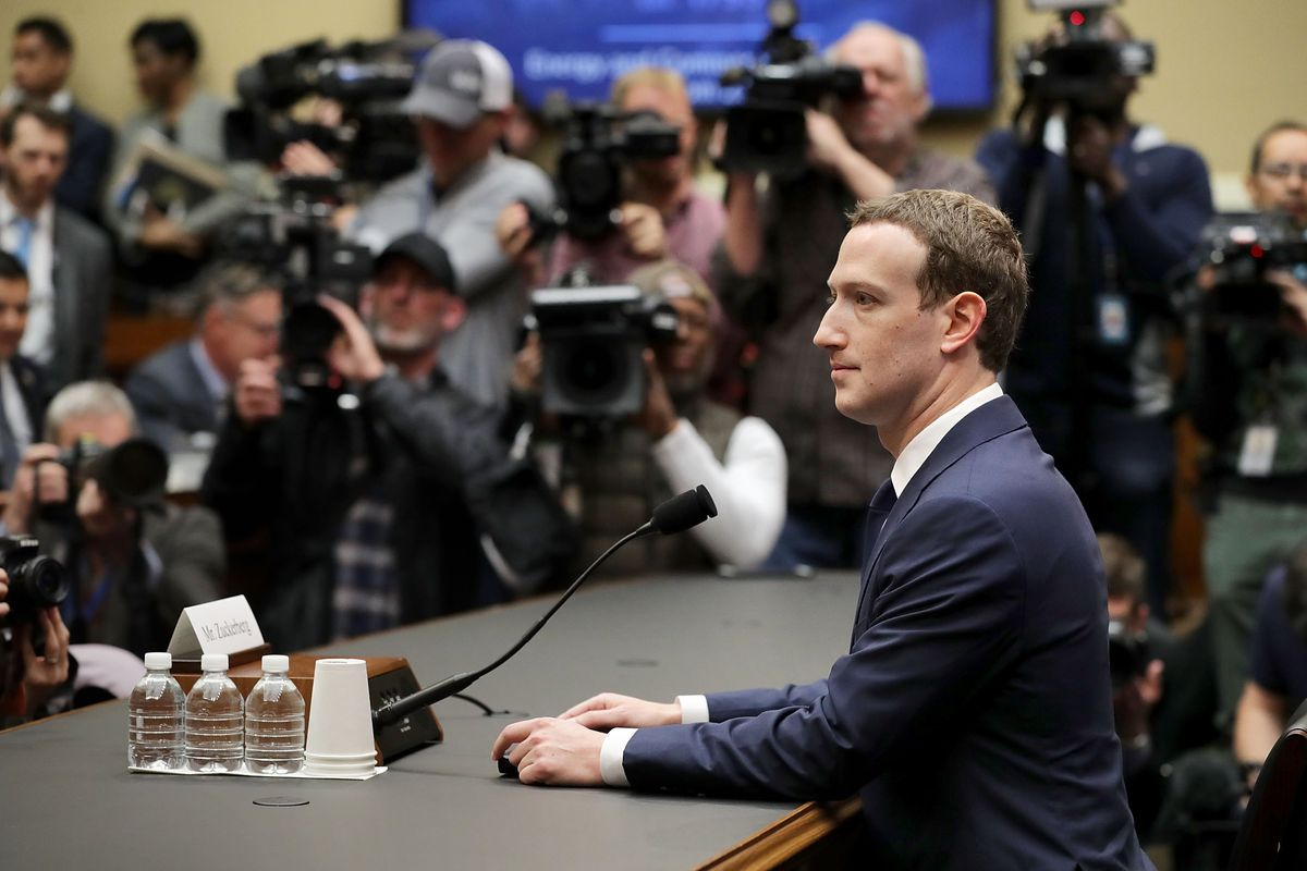 Mark Zuckerberg testifies before a House committee, surrounded by photographers