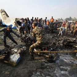 Nepalese police salvage debris at the crash site of a Sita Air airplane near Katmandu, Nepal, early Friday, Sept. 28, 2012.  The plane carrying trekkers into the Everest region crashed just after takeoff Friday morning in Nepal's capital, killing all 19 people on board, authorities said.