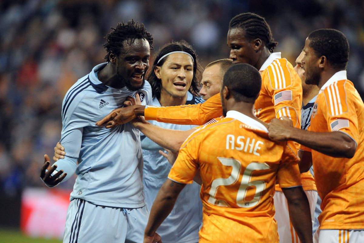 Sep 14, 2012; Kansas City, KS, USA; Sporting KC forward Kei Kamara (left) and Houston Dynamo defender Corey Ashe (26) argue in the second half at Livestrong Sporting Park. The game ended in a 1-1 tie. Mandatory Credit: John Rieger-US PRESSWIRE