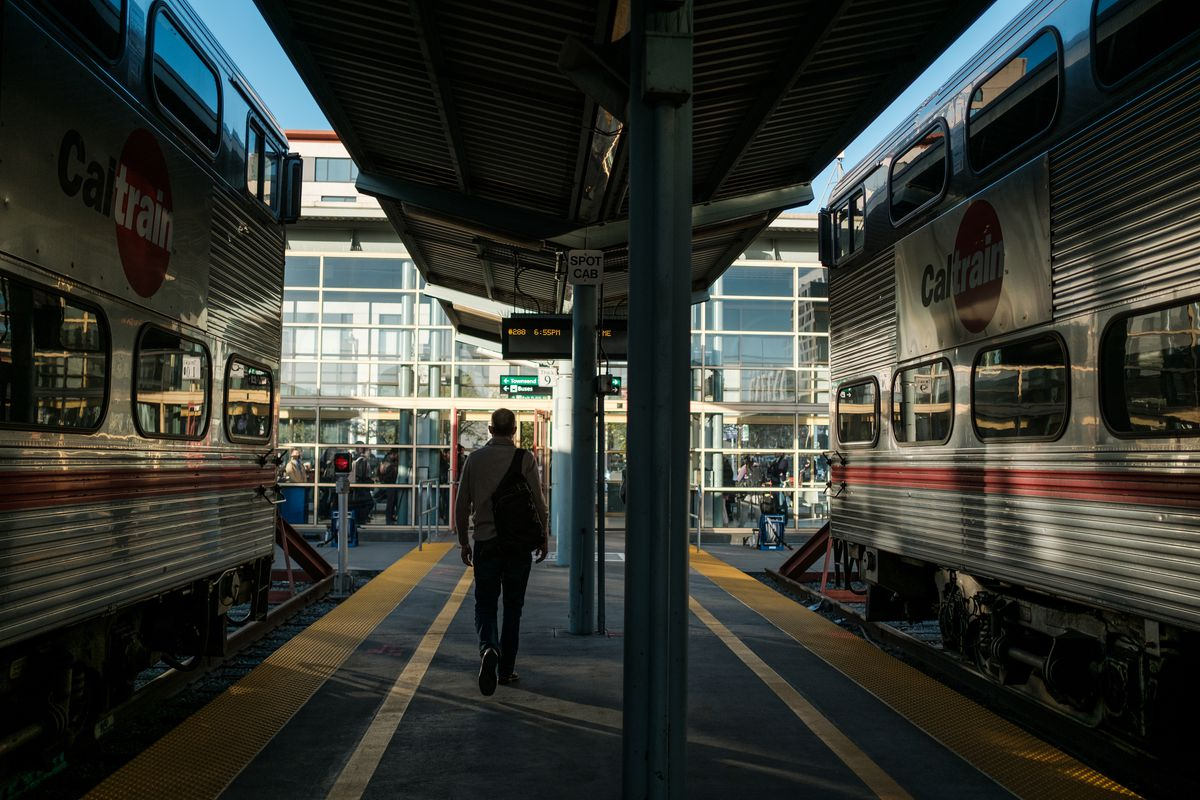 A person walking on the Caltrain platform between two trains.