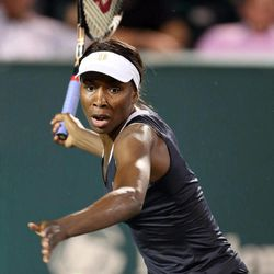 Venus Williams returns a shot to Jelena Jankovic, of Serbia, at the Family Circle Cup tennis tournament in Charleston, S.C., Wednesday, April 4, 2012.
