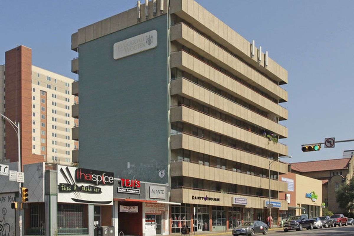 Seven-story modernist building, blocky, balconies across front of each floor