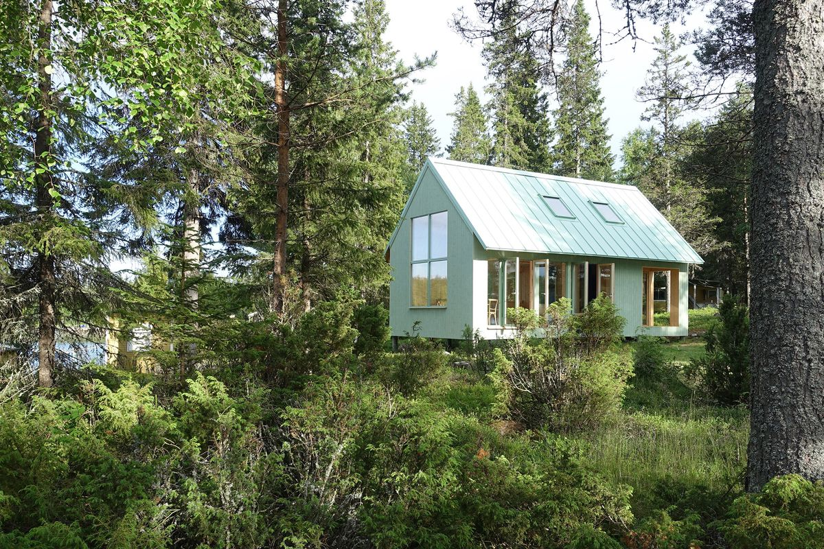 Mint green house covered in windows in the woods.