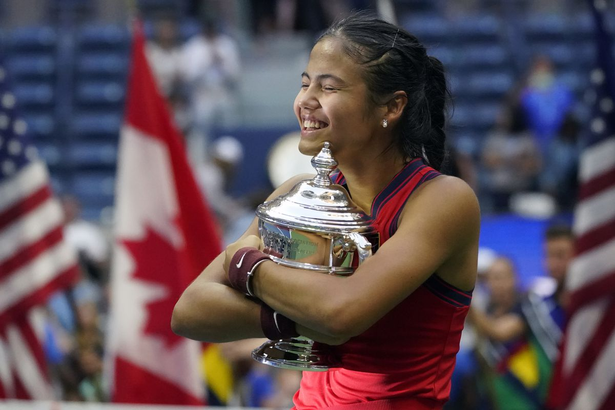 Emma Raducanu, of Britain, hugs the US Open championship trophy after defeating Leylah Fernandez, of Canada, in the women's singles final.