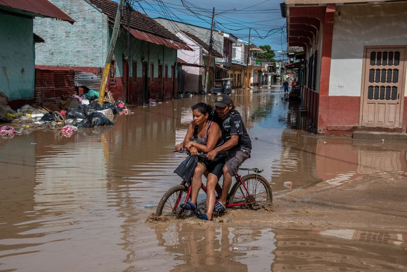 A man and woman ride their bike through flooded streets.