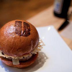 "Umami Burger burger (with branded bun) by <a href=""http://www.flickr.com/photos/cozysf/6291629965/in/pool-520531@N21/"">cozysf</a>."