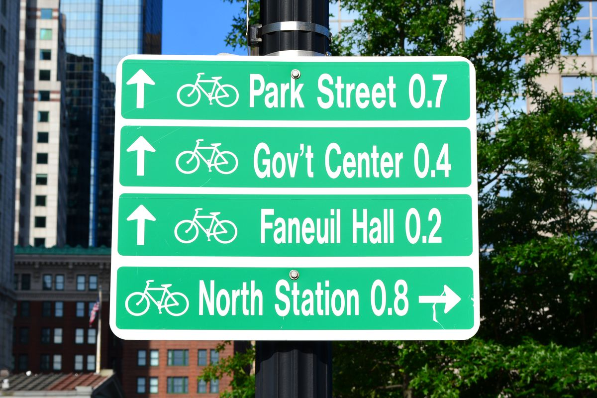 A street sign showing the distances for bikers to certain Boston destinations.