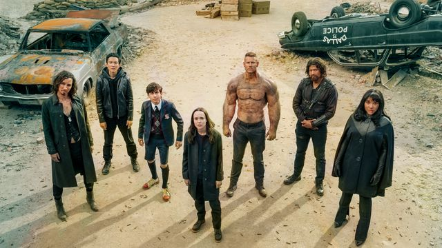 the umbrella academy family stands in a car junkyard ready for battle