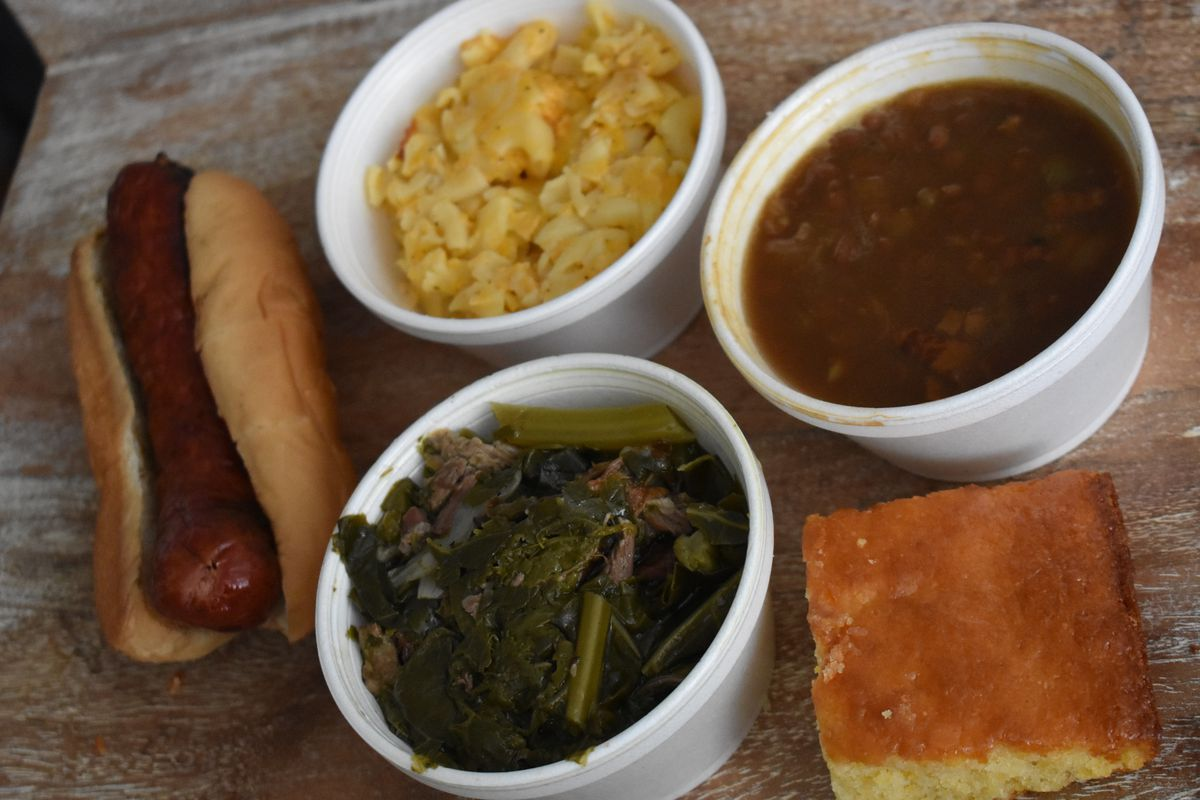 A sausage link in a hot dog bun is accompanied by three small white styrofoam bowls of collards, mac and cheese, and beans. There's also a slice of cornbread.