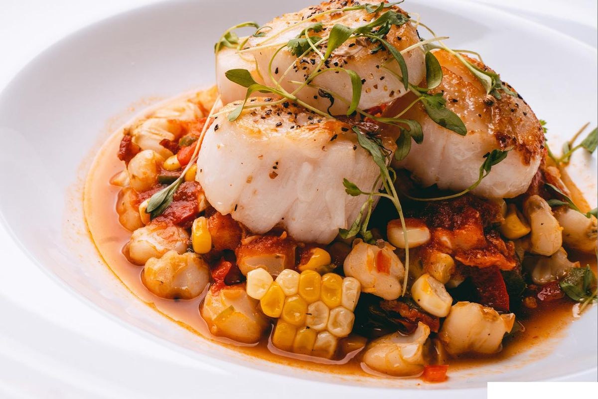 A dish of corn, mixed vegetables topped with three seared scallops