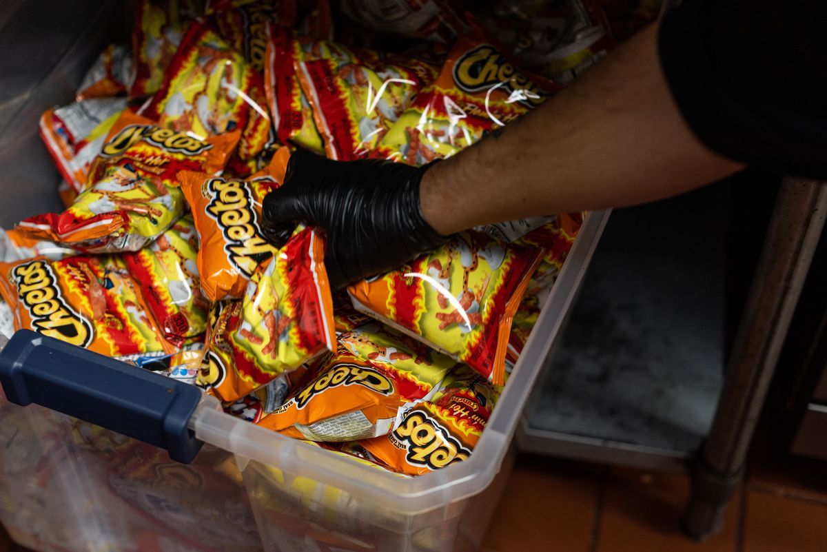 A worker hand in a black glove reaches in to a bin filled with Hot Cheetos.