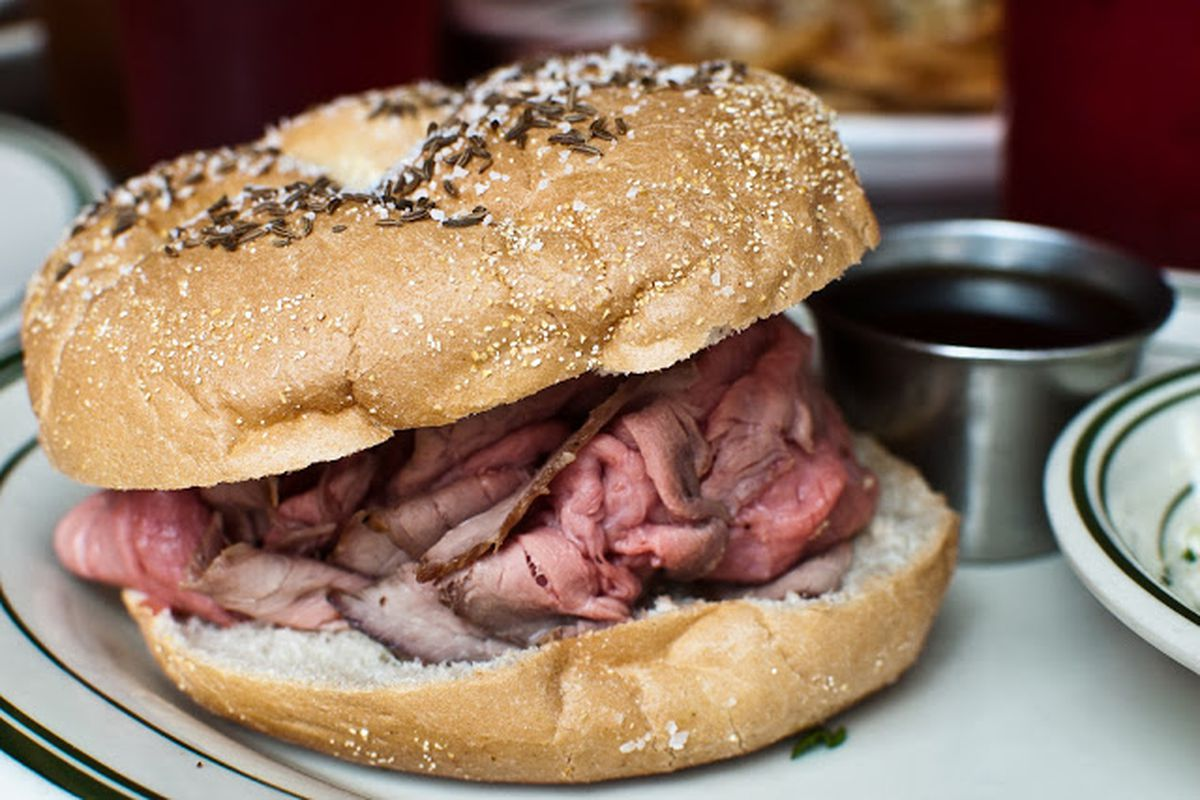 A beef on weck sandwich with rare roast beef on a kimmelweck bun and a silver cup of au jus