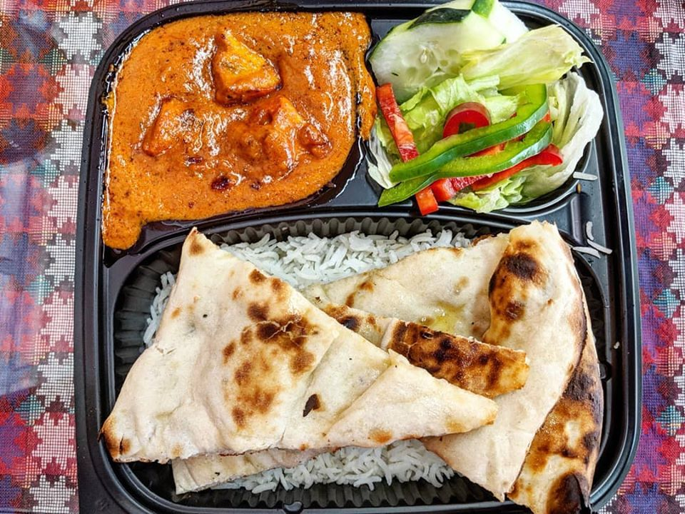 Chicken tikka masala, salad, rice, and naan in a black takeout tray on a colorful tablecloth
