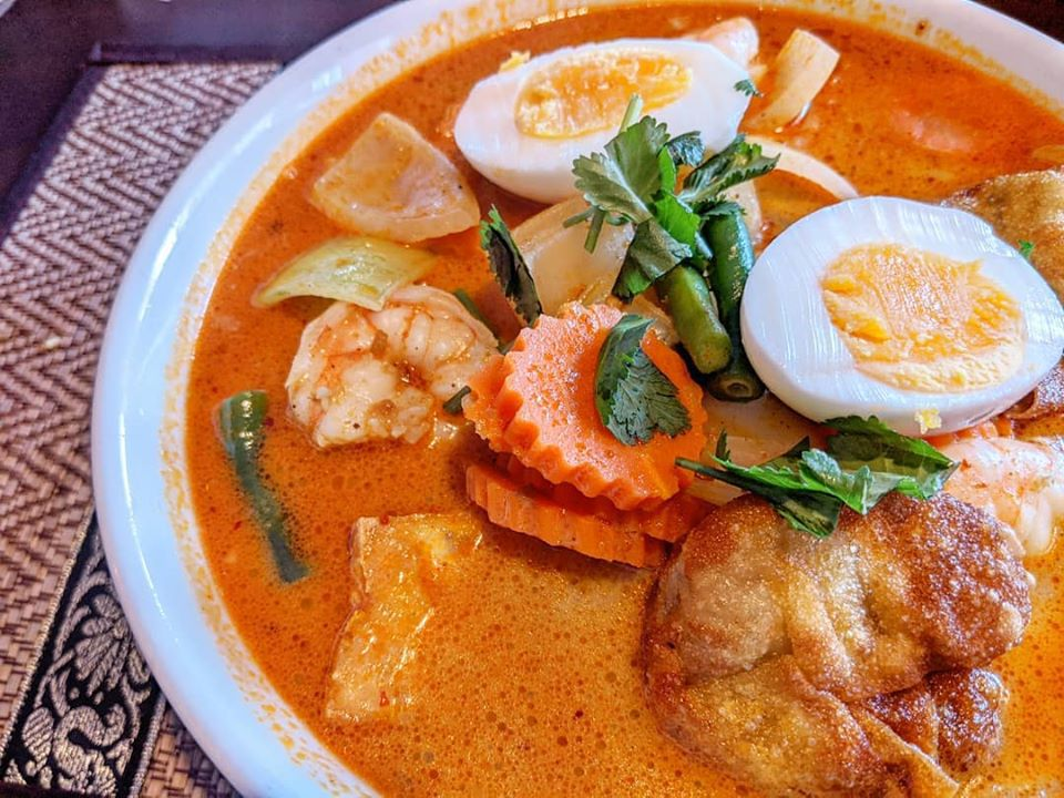 Bowl of a yellow-orange curry with a sliced hard-boiled egg, shrimp, sliced carrots, tofu, and more