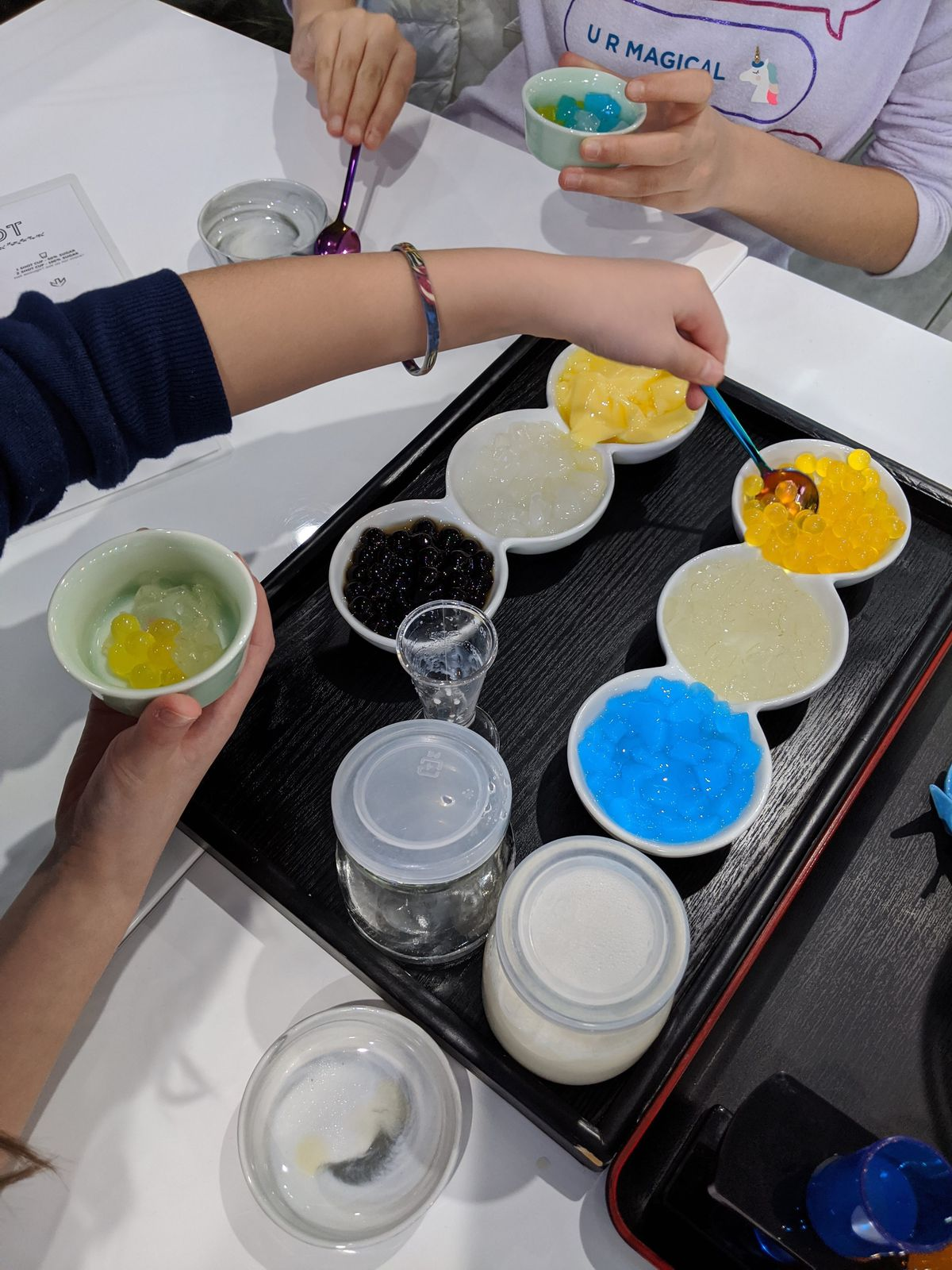 Customers add boba toppings to their own individual cups