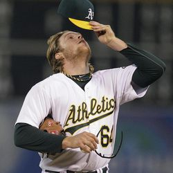 Oakland Athletics' A.J. Griffin adjusts his cap in the first inning of a baseball game against the Seattle Mariners on Friday, Sept. 28, 2012, in Oakland, Calif.
