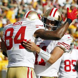 San Francisco 49ers' Randy Moss (84) is congratulated by quarterback Alex Smith (11) after Moss caught a touchdown pass during the first half of an NFL football game against the Green Bay Packers Sunday, Sept. 9, 2012, in Green Bay, Wis.