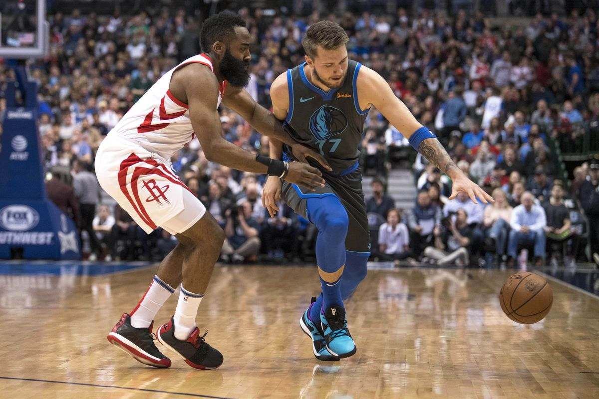 Houston Rockets guard James Harden and Dallas Mavericks forward Luka Doncic fight for a loose ball during the first quarter at the American Airlines Center.