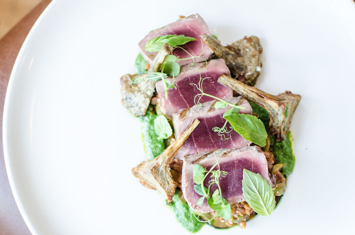 Four slices of rare tuna sit on a bed of roasted eggplant and green olives on a white plate. Crispy artichokes and fresh herbs garnish the plate.