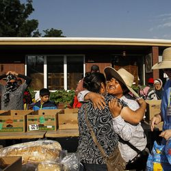Blanca Quispe, right, hugs a refugees as others line up for clothes and food at the Mosaic Inter-Faith center in Salt Lake City on Thursday, Aug. 4, 2016.